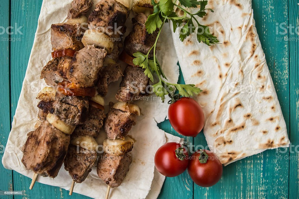 Pork cooked with vegetables on skewers  a turquoise table. Wooden stock photo