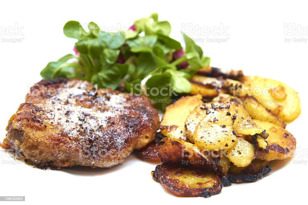 Pork cutlet with fried potatoes and lettuce stock photo