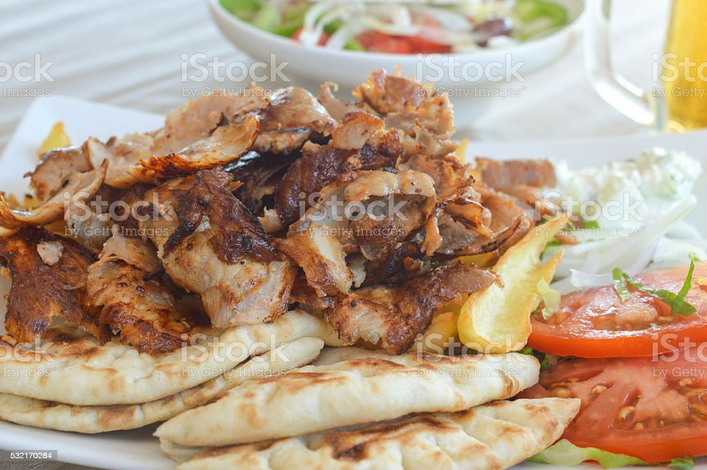 Pork gyros on a plate with salad and a bear stock photo