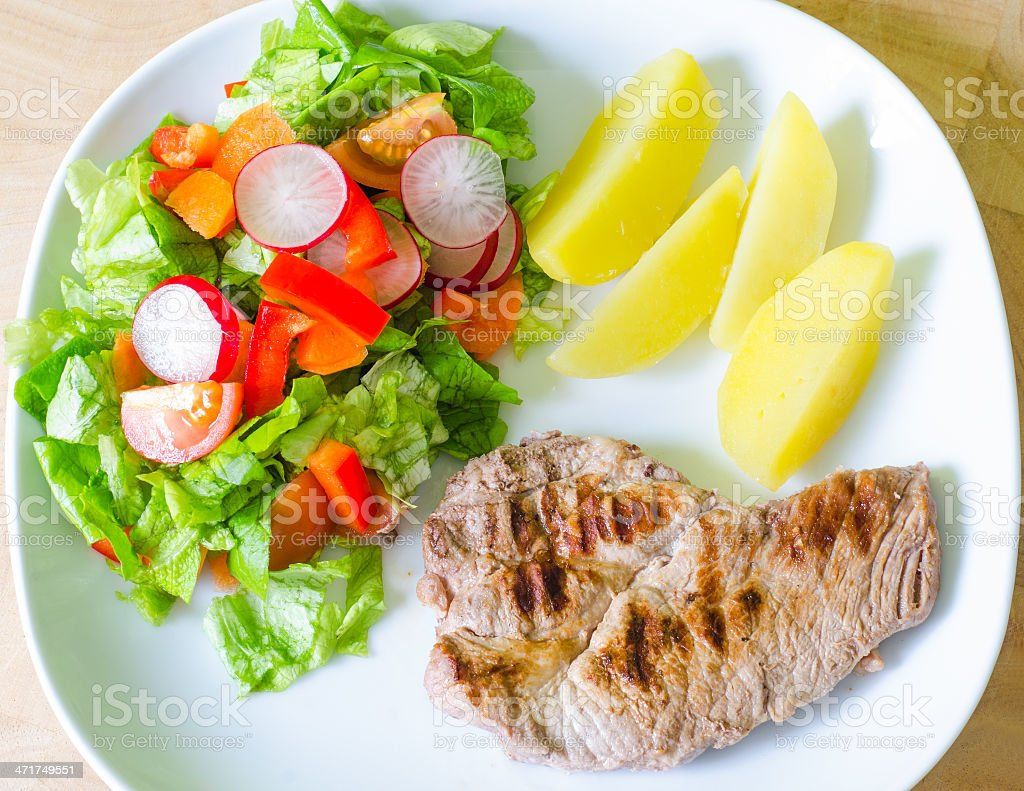 Pork meat with salad and potatoes royalty-free stock photo