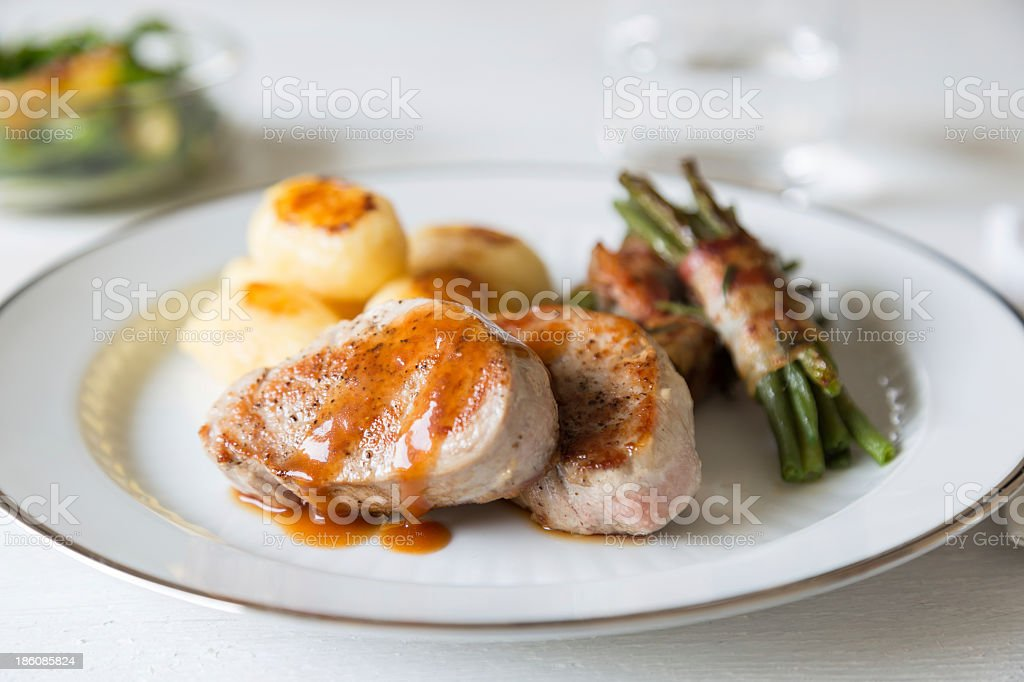 Pork medallions with potatoes and beans on white plate stock photo