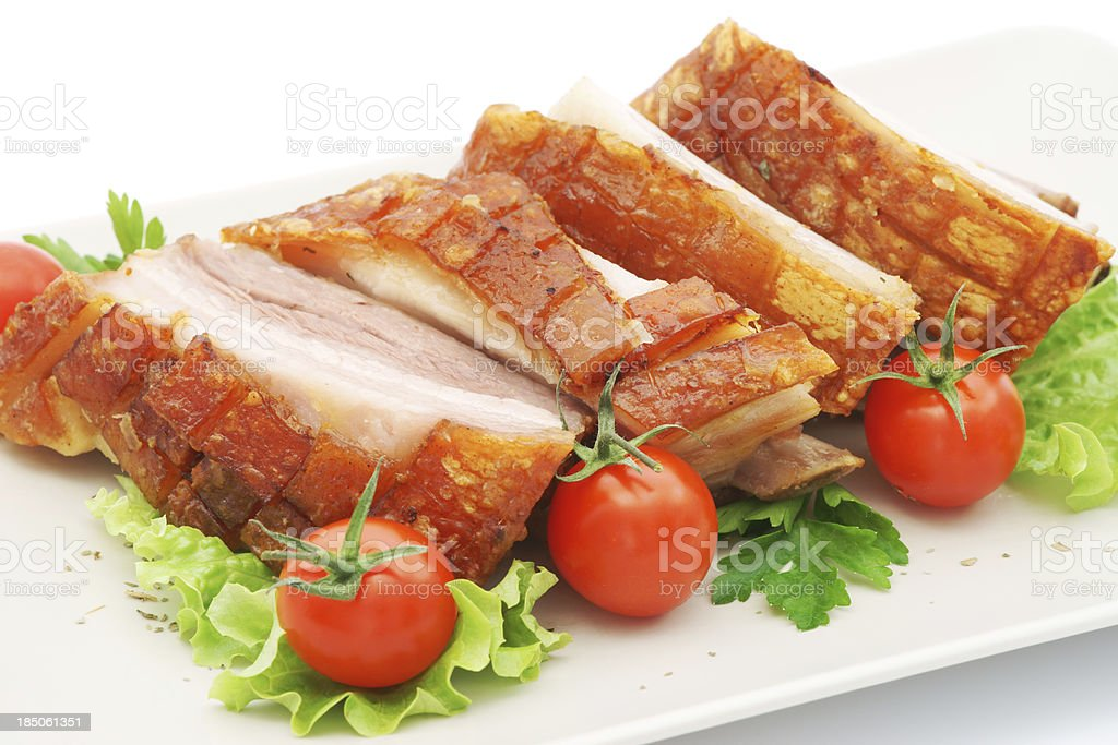 Pork ribs with tomato, salad and parsley on plate isolated stock photo