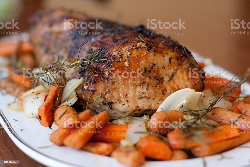Pork roast with carrots on platter stock photo
