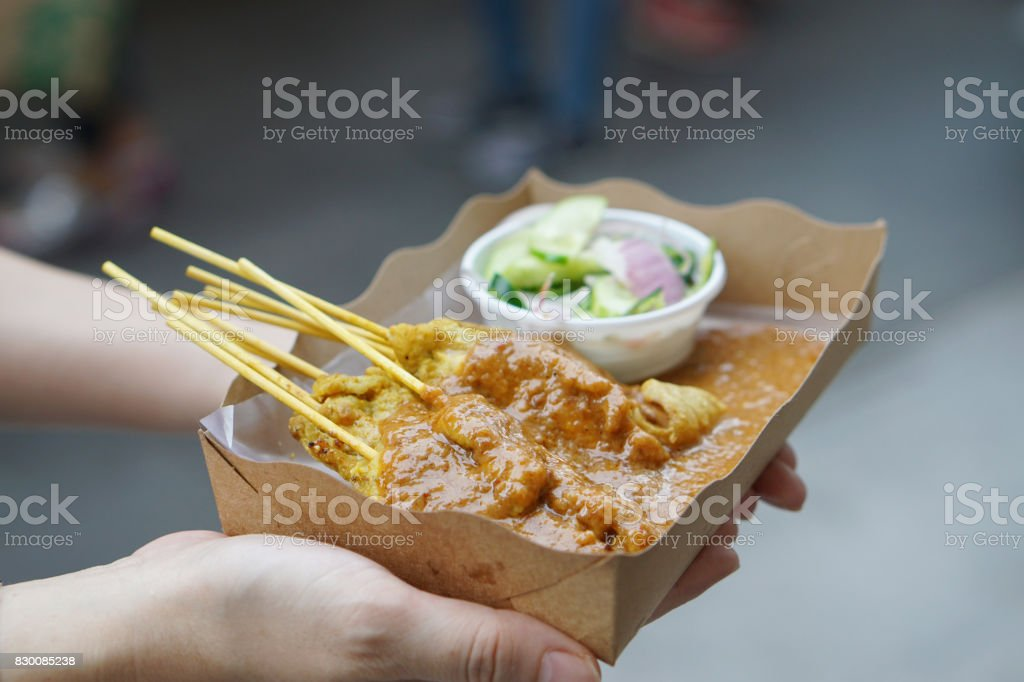 Pork Satay with peanut sauce, served with pickles which are cucumber slices and onions in vinegar. stock photo