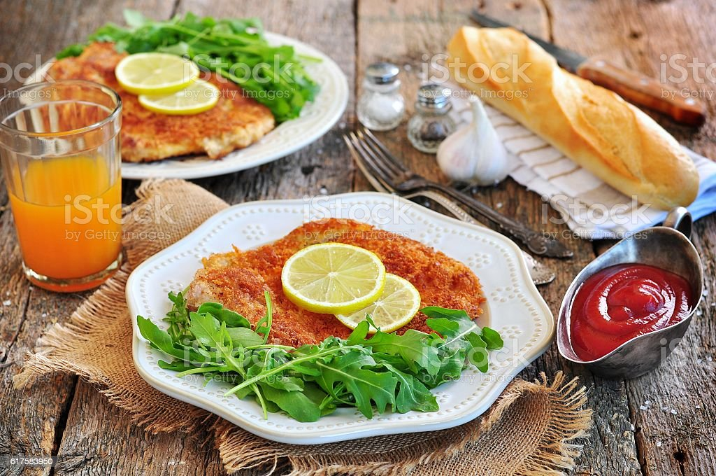 Pork schnitzel with organic arugula and lime stock photo