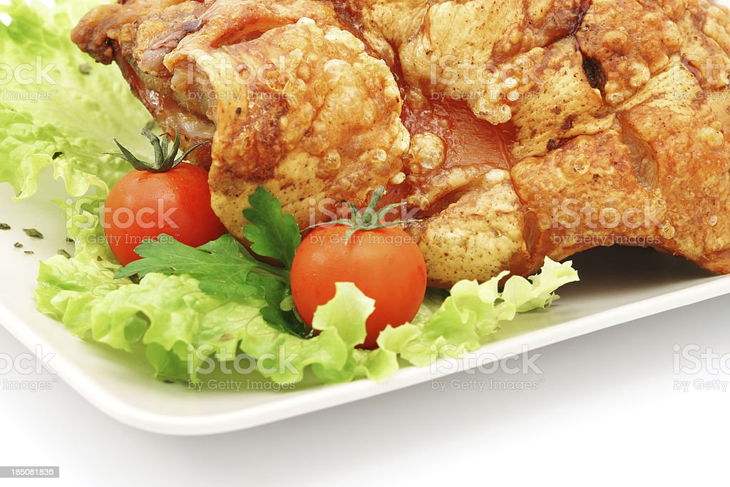 Pork shank close-up on plate with tomato and salad isolated royalty-free stock photo