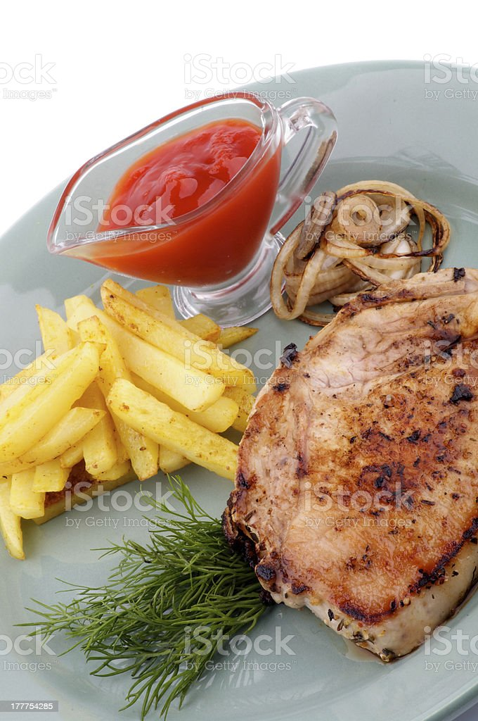 Pork Steak, French Fries and Grilled Onions royalty-free stock photo