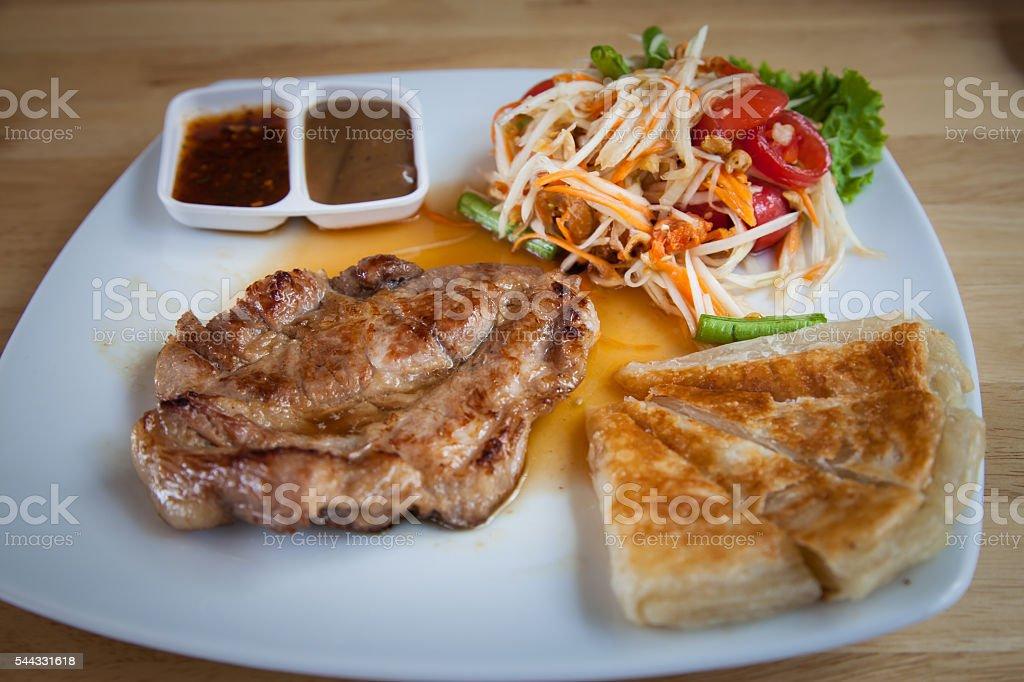 Pork steak with roti and Thai papaya salad. stock photo