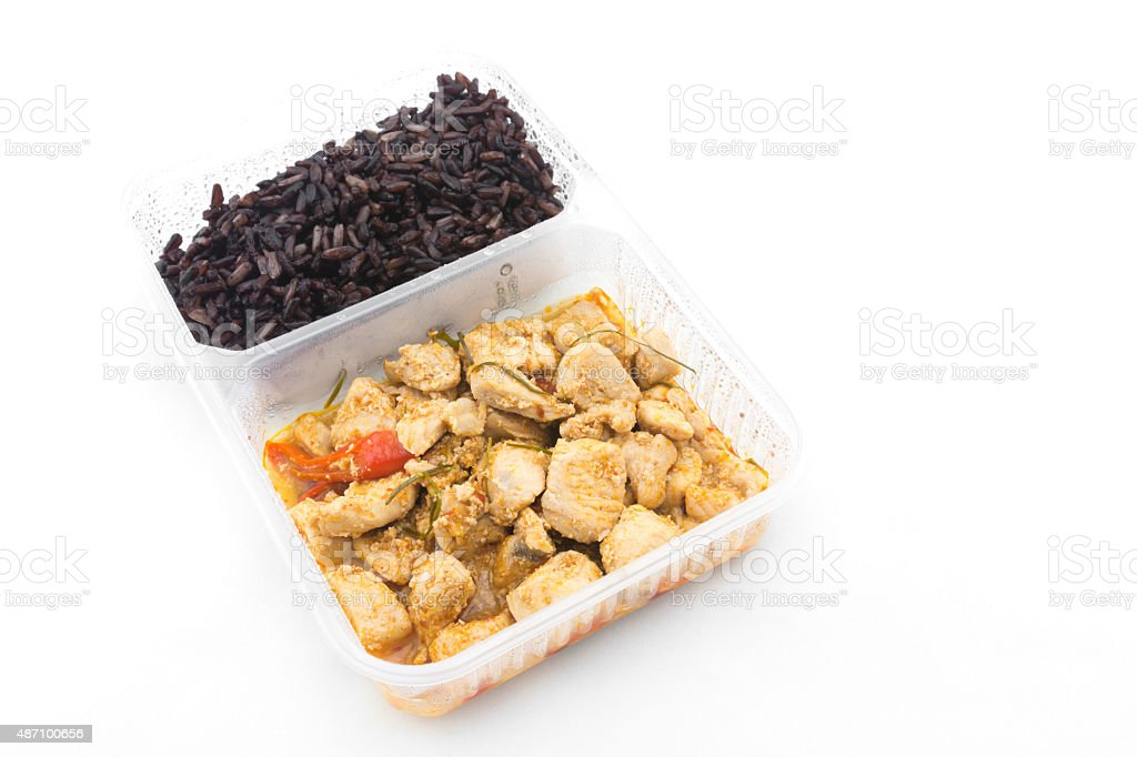Pork stir-fried in spicy coconut cream curry with Riceberry stock photo