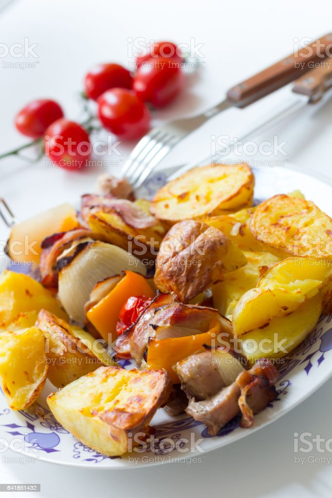 Porky skewer with potato wedges stock photo