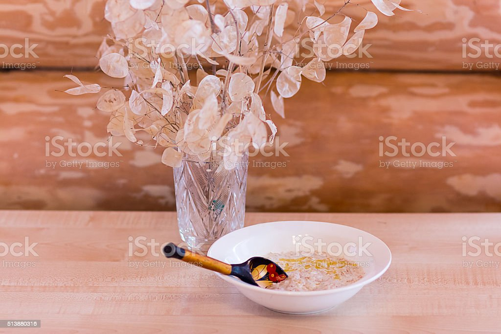 porridge with butter and a wooden spoon stock photo