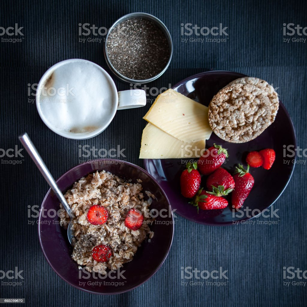 Porridge with strawberries close-up. Flakes are polly, oatmeal with strawberries. Cheese, bread  and  cappuccino   Healthy diet, diet, vitamins stock photo