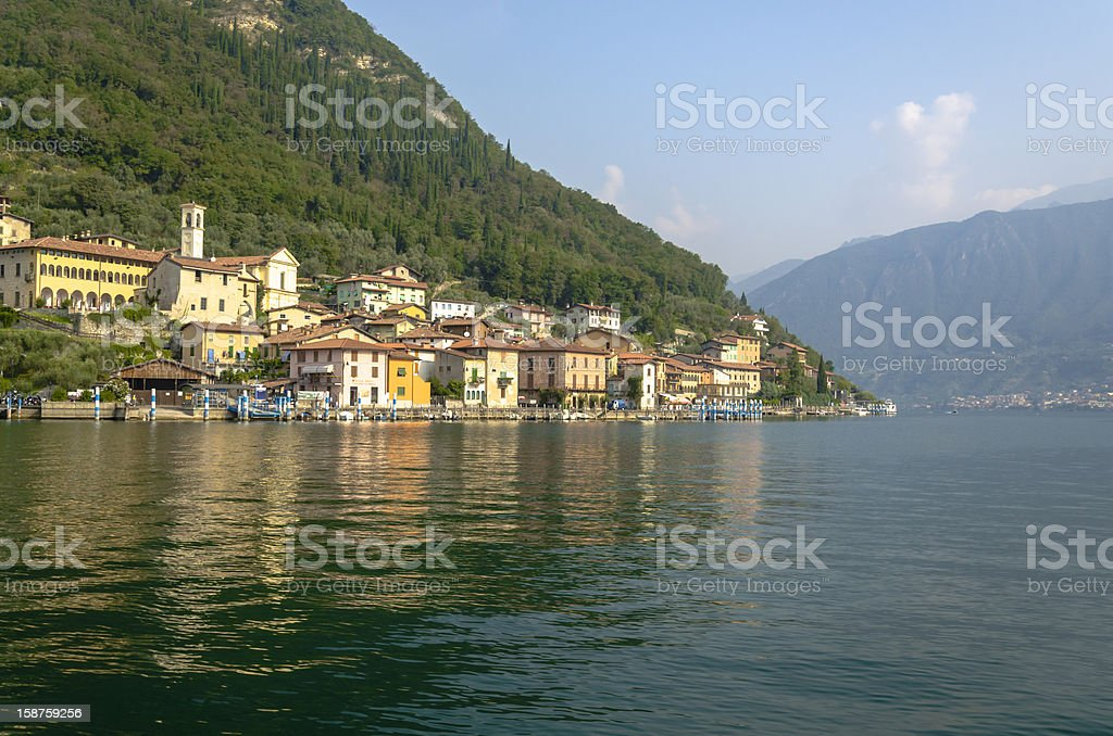 port and mountains reflected in water, lake Iseo, Monte Isola stock photo