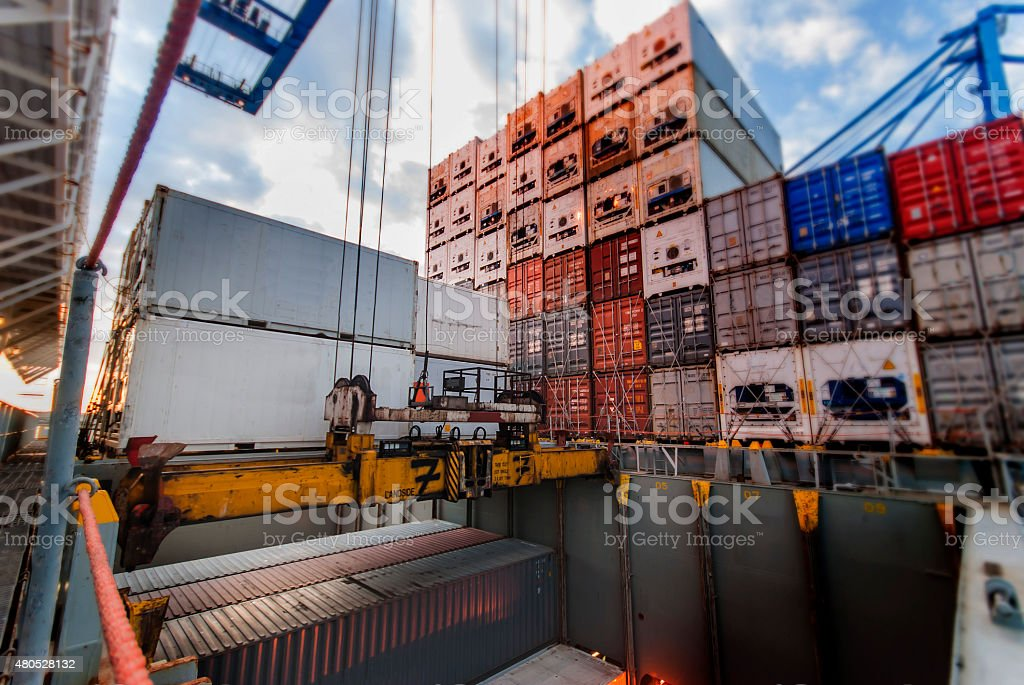 Port crane lifts container during cargo operation stock photo