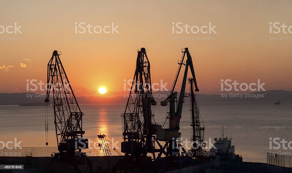 Port cranes on background of rising sun royalty-free stock photo