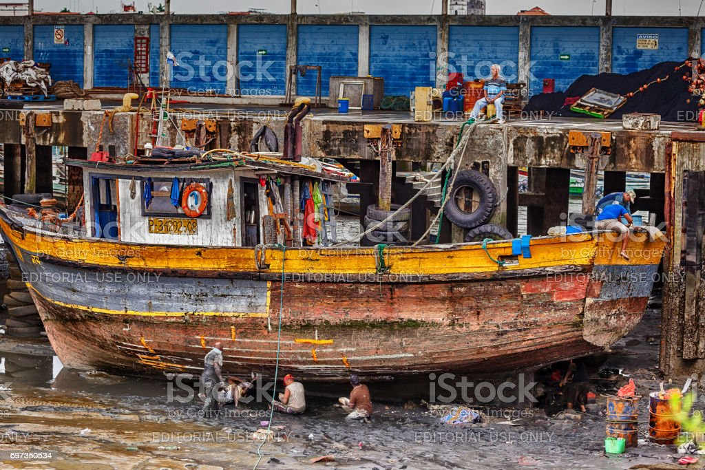 Port workers repair a fishing boat in the fishing port of Panama City. stock photo