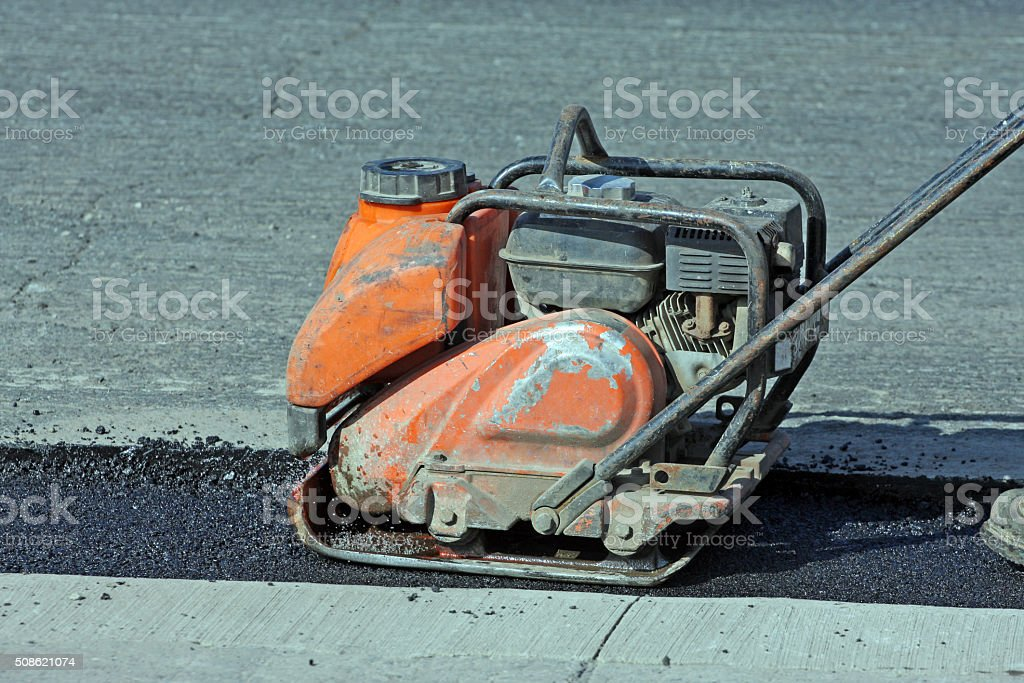 Portable Construction Compactor Compacting Asphalt On A Road Repair Site stock photo