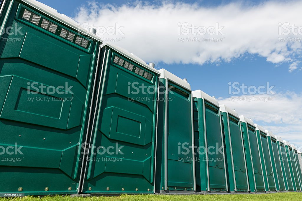 portable plastic festival toilet cubicles in a field stock photo