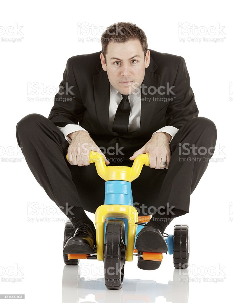 Portait of a businessman riding tricycle stock photo