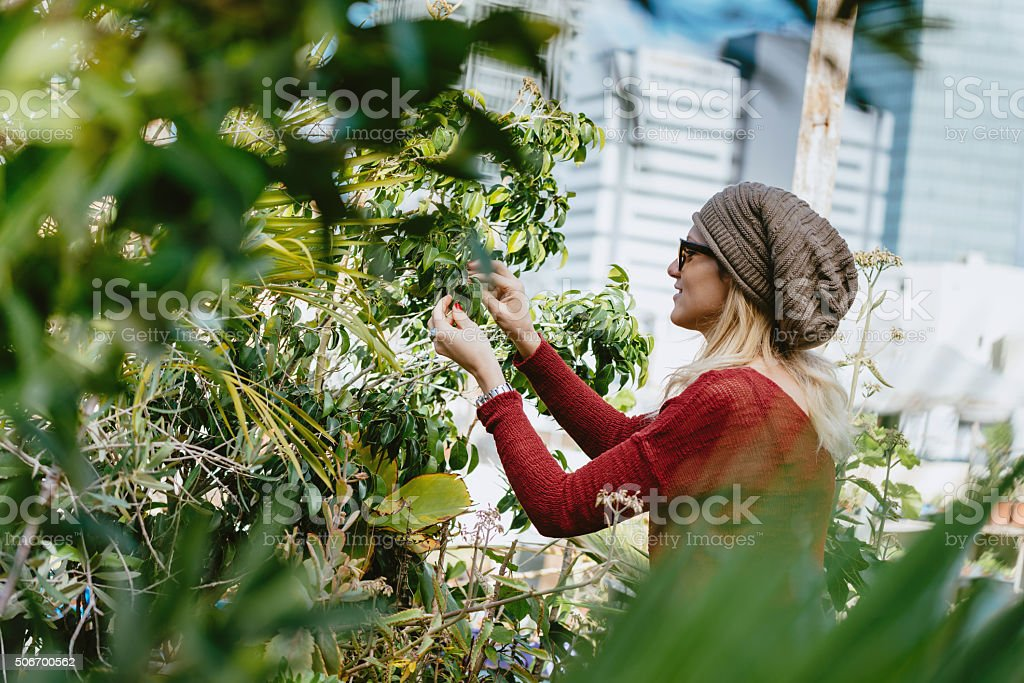 Portait of beauiful woman in roof garden with flowers stock photo