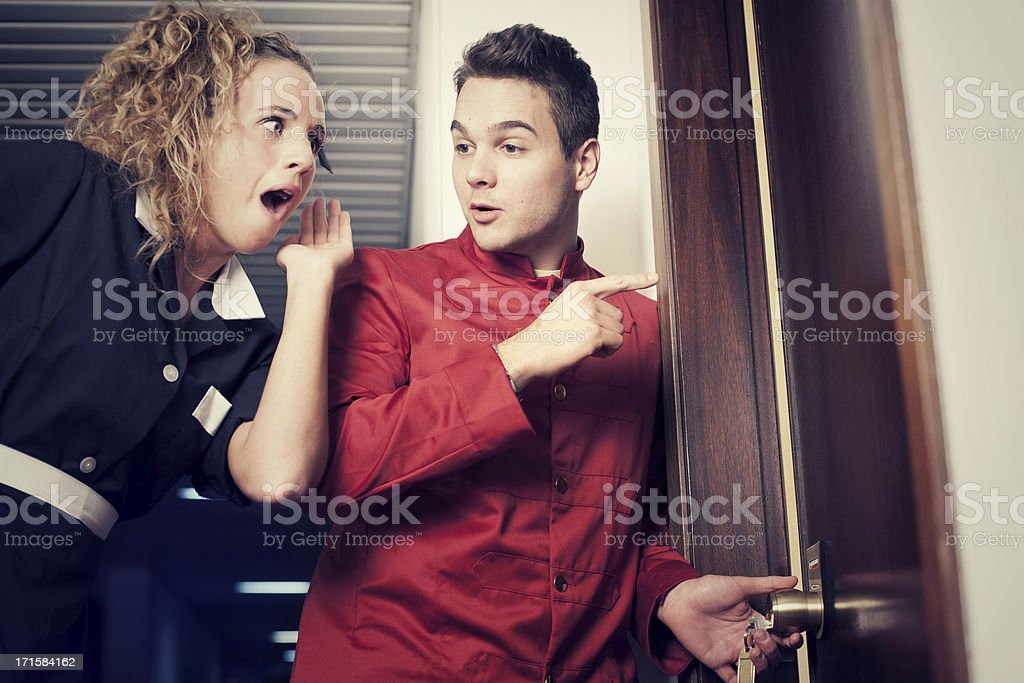 Porter and hotel maid eavesdropping at the door royalty-free stock photo