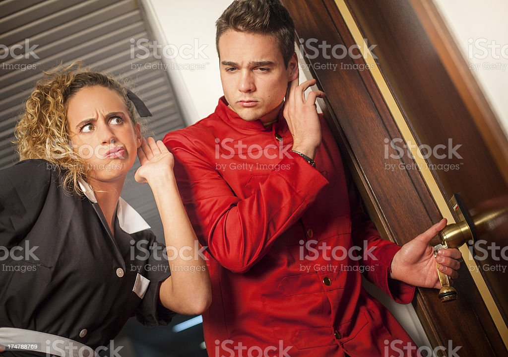 Porter and hotel maid eavesdropping at the door stock photo