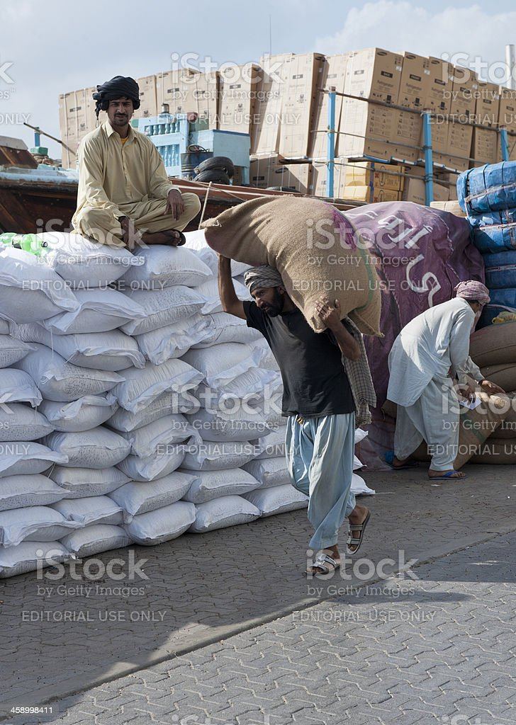porter carrying bag on shoulder in Dubai Creek stock photo