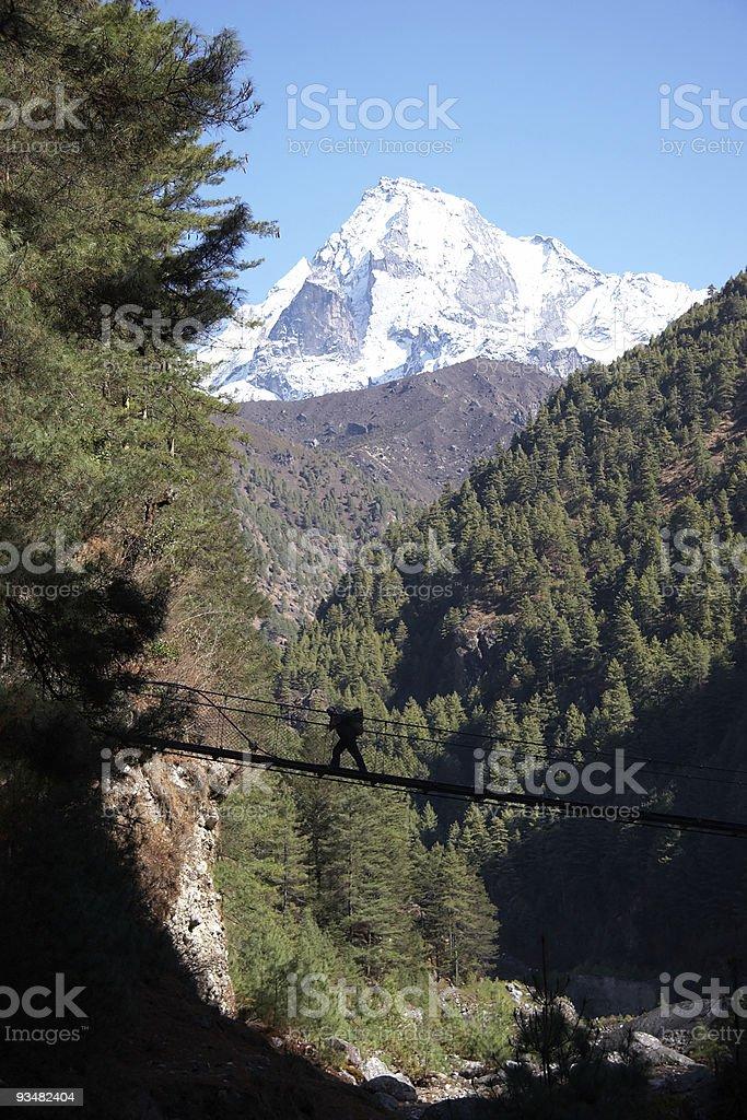 Porter crossing rope bridge in Himalaya, Nepal royalty-free stock photo