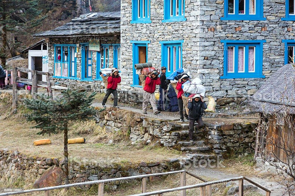 Porters of Himalaya Mountain expedition walking throw village stock photo