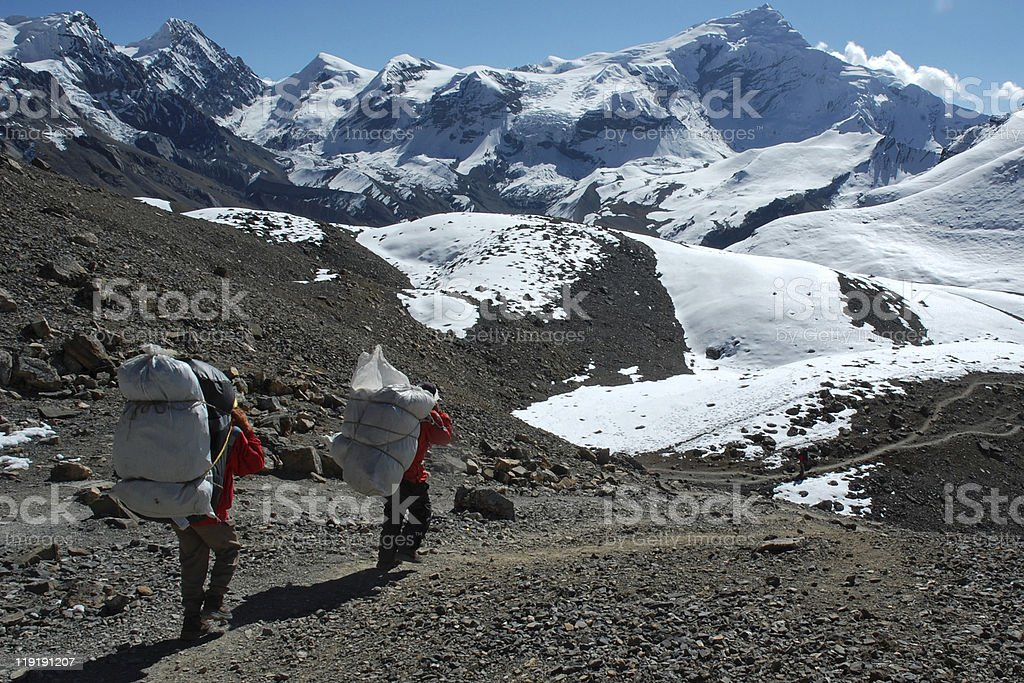 Porters on the way down to Manang stock photo