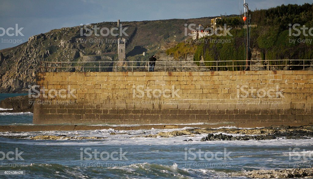 Porthleven pier with cliffs, tin mine workings behind; Cornwall stock photo