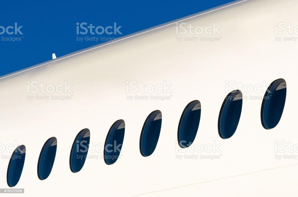 Portholes on white modern airplane and sky stock photo