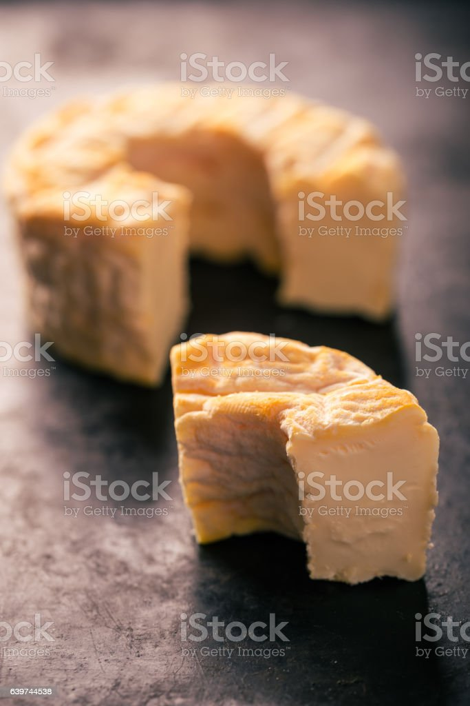 Portion cut from whole camembert cheese with golden color stock photo