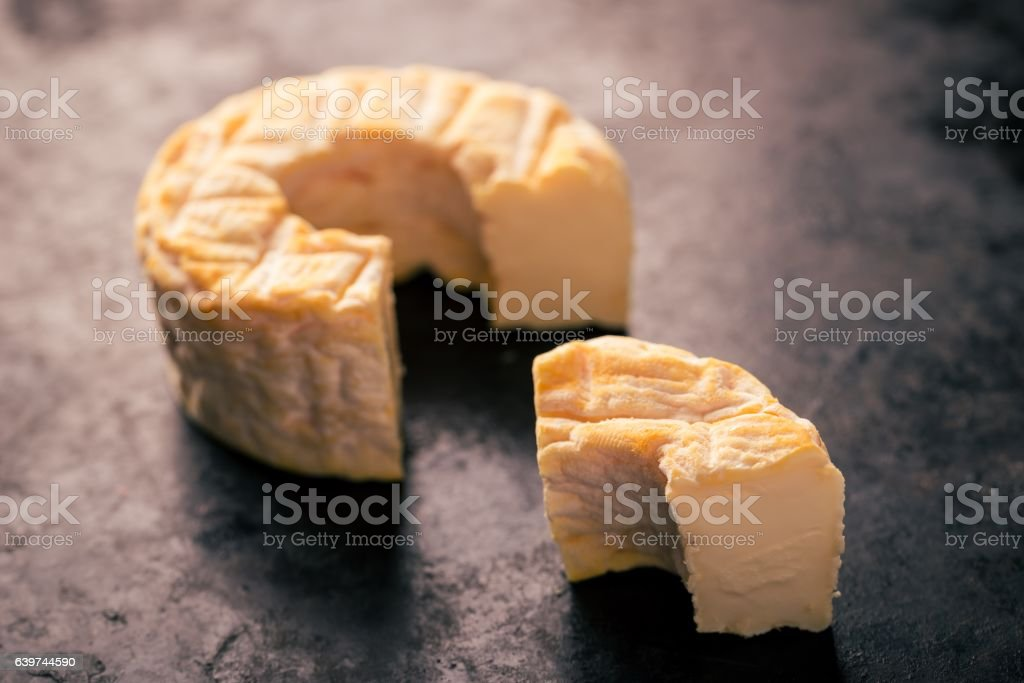 Portion cut from whole camembert cheese with orange color stock photo