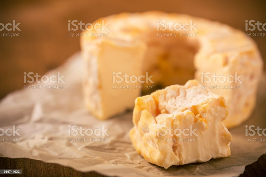 Portion cut from whole golden camembert cheese on crumpled paper stock photo
