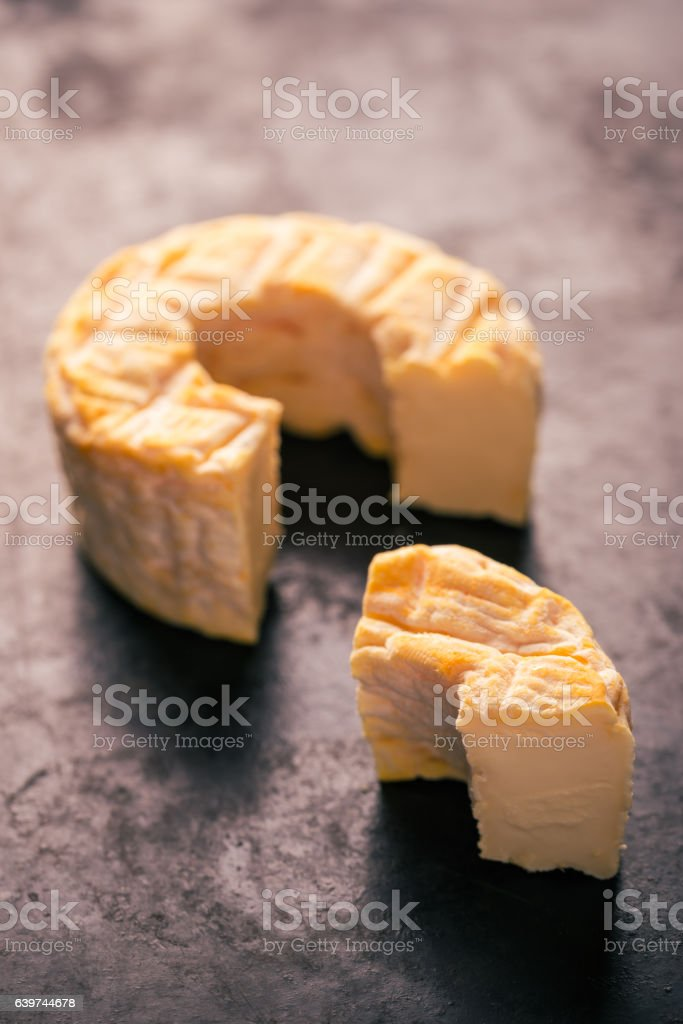 Portion cut from whole golden camembert cheese on dark tray stock photo
