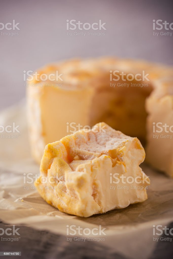 Portion cut from whole golden camembert cheese on grey board stock photo