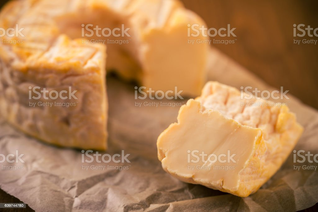 Portion cut from whole golden camembert cheese on paper sheet stock photo