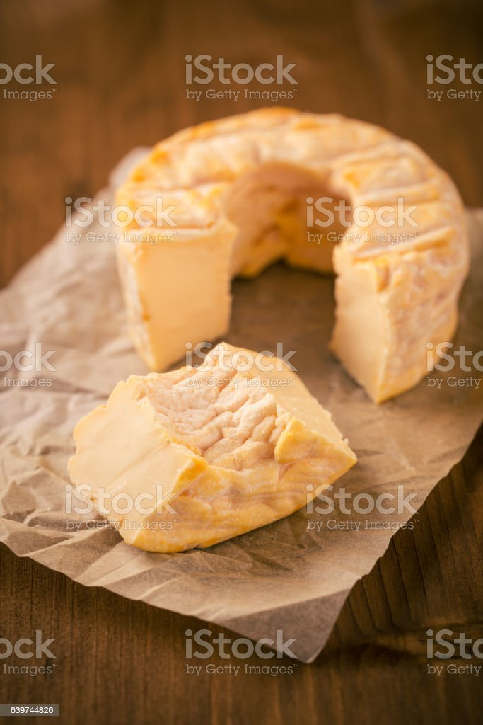 Portion cut from whole golden camembert cheese on wooden board stock photo
