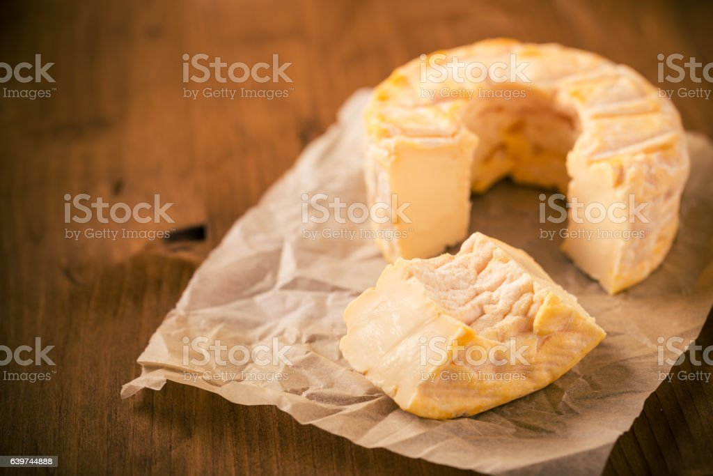 Portion cut from whole golden camembert cheese on wooden table stock photo