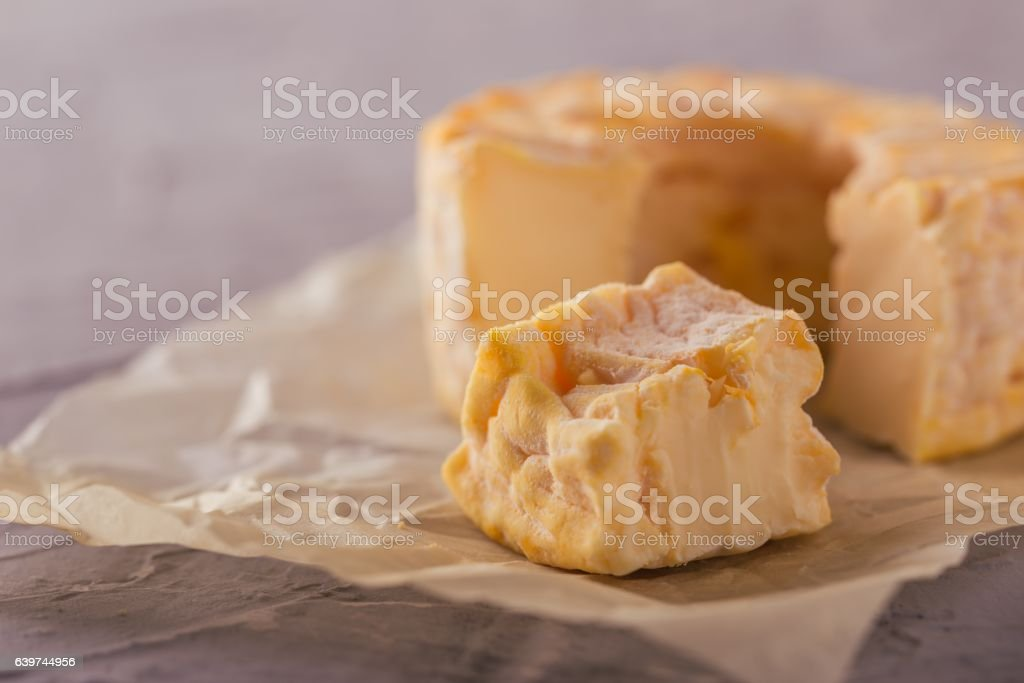 Portion cut from whole golden camembert on grey board stock photo