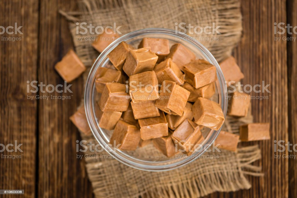 Portion of Caramel pieces on wooden background (selective focus) stock photo