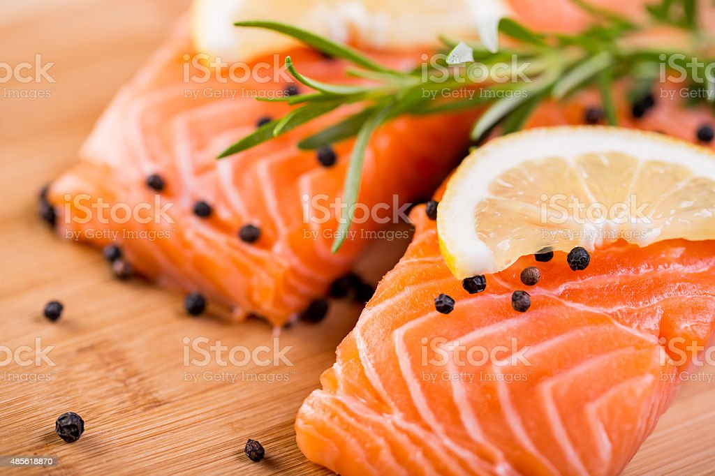 Portion of fresh salmon fillet with pepper and rosemary stock photo