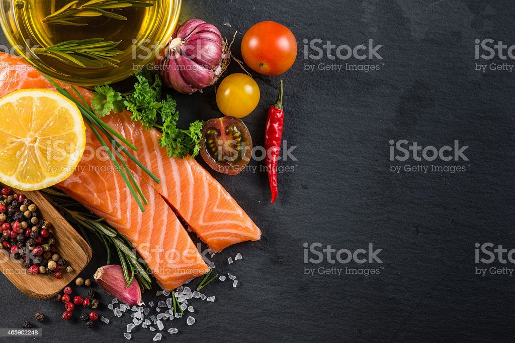 Portion of fresh salmon with spices,herbs and vegetables stock photo