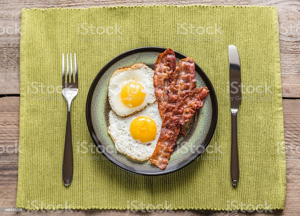 Portion of fried eggs with bacon stock photo