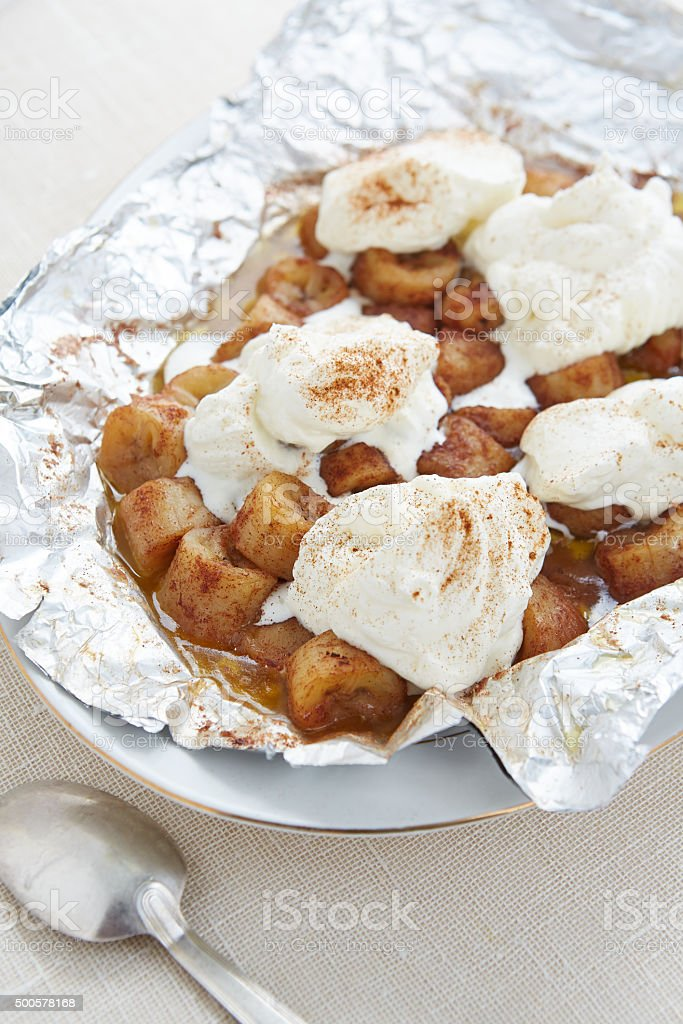 portion of grilled bananas with whipped cream stock photo
