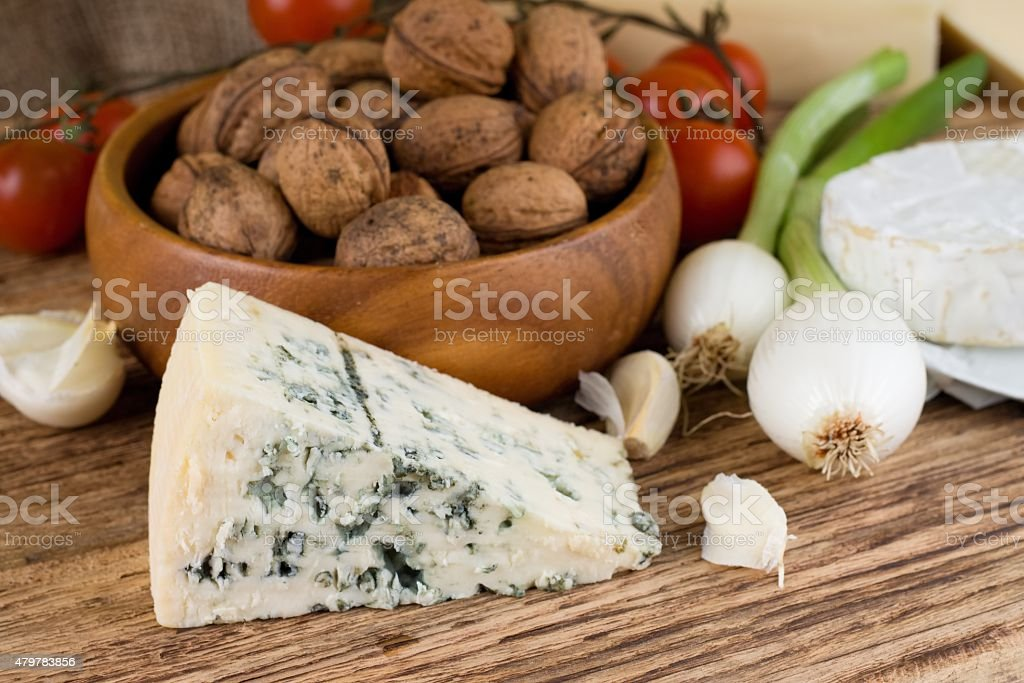 Portion of Niva danish blue cheese next to various vegetable stock photo