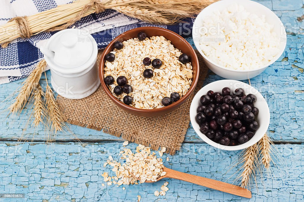Portion of oatmeal in the bowl with black chokeberry stock photo