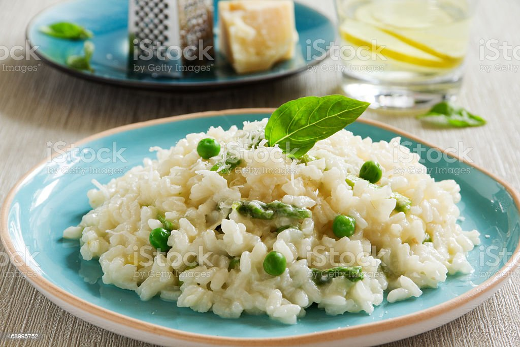A portion of risotto with asparagus and peas on a blue plate stock photo