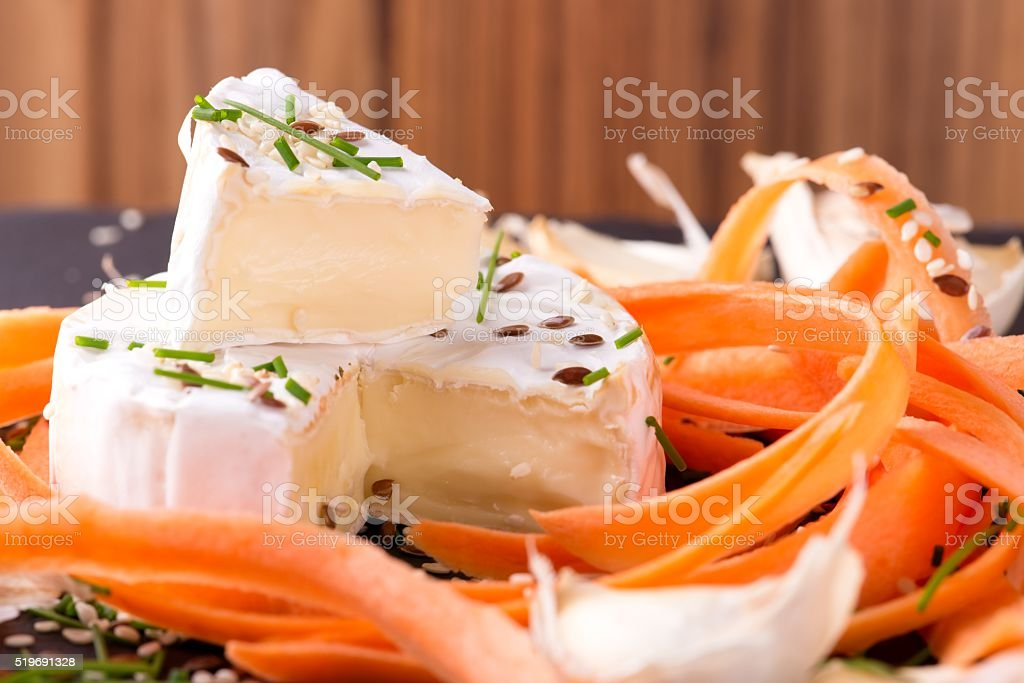 Portion of white camembert with carrot and chive stock photo